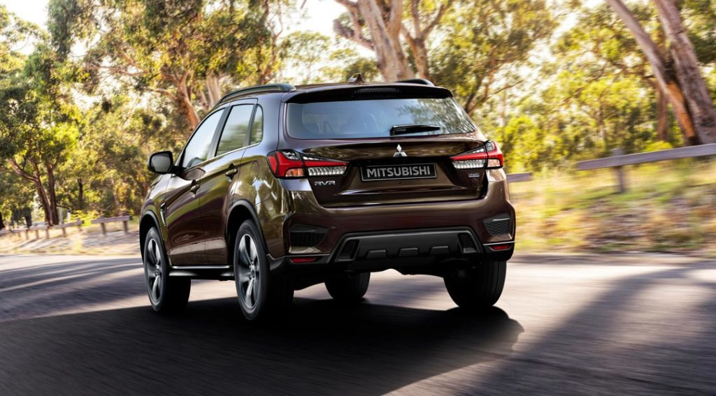 Mitsubishi RVR 2021 en Oak Brown sur une route en bordure d'arbre