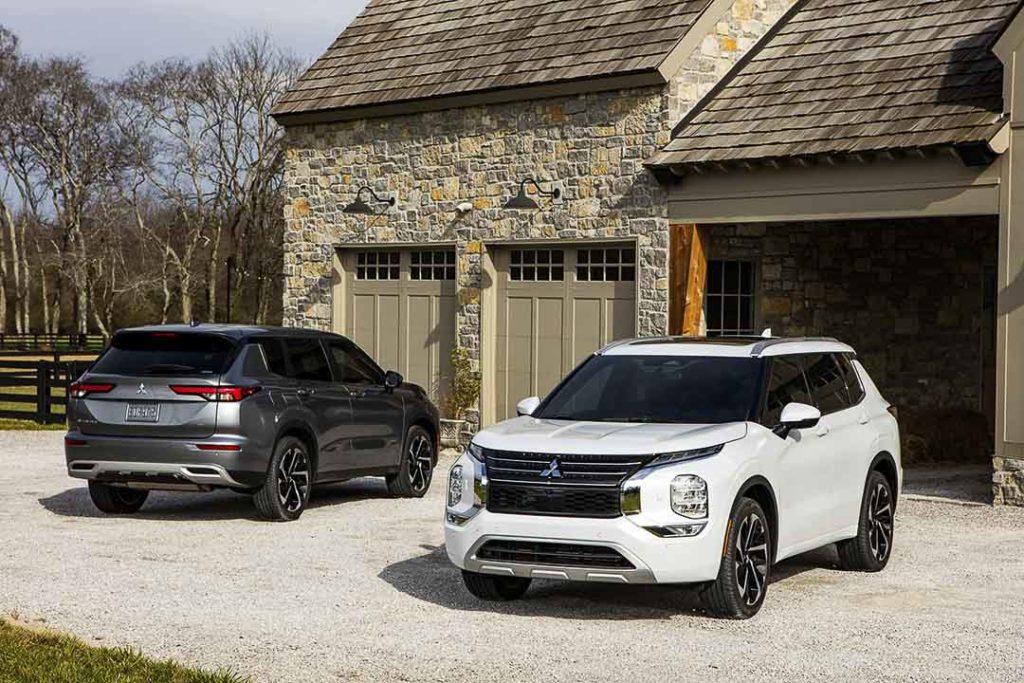 vu avant et arrière de deux Mitsubishi Outlander 2022 stationné devant une maison
